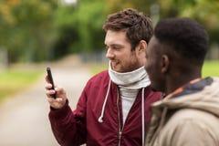 Amis heureux avec le smartphone dehors Image stock
