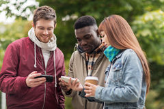 Amis heureux avec le smartphone et le café dehors Photos stock