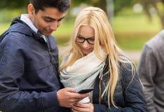 Amis heureux avec le smartphone et le café dehors Photographie stock libre de droits