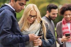 Amis heureux avec le smartphone et le café dehors Images libres de droits