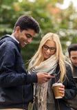 Amis heureux avec le smartphone et le café dehors Image libre de droits