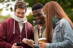 Amis heureux avec le smartphone et le café dehors Photo stock