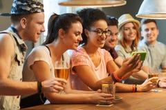 Amis heureux avec le smartphone prenant le selfie à la barre Image stock