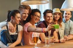 Amis heureux avec le smartphone prenant le selfie à la barre Image libre de droits