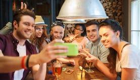 Amis heureux avec le smartphone prenant le selfie à la barre Images libres de droits