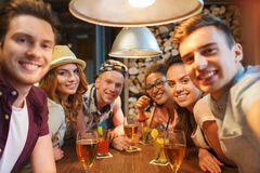 Amis heureux avec le smartphone prenant le selfie à la barre Photographie stock