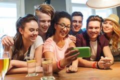 Amis heureux avec le smartphone prenant le selfie à la barre Photos stock