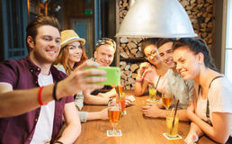 Amis heureux avec le smartphone prenant le selfie à la barre Photo libre de droits