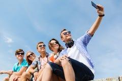 Amis heureux avec le smartphone prenant le selfie Image stock