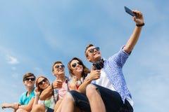 Amis heureux avec le smartphone prenant le selfie Images libres de droits