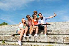 Amis heureux avec le smartphone prenant le selfie Photo libre de droits