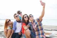 Amis heureux avec le smartphone prenant le selfie Photos libres de droits