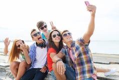 Amis heureux avec le smartphone prenant le selfie Images stock