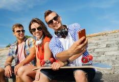 Amis heureux avec le smartphone prenant le selfie Photographie stock libre de droits