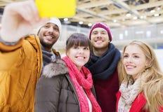 Amis heureux avec le smartphone sur la piste de patinage Image stock