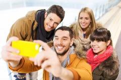 Amis heureux avec le smartphone sur la piste de patinage Images libres de droits