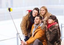 Amis heureux avec le smartphone sur la piste de patinage Photos stock