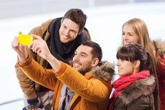 Amis heureux avec le smartphone sur la piste de patinage Photographie stock