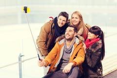 Amis heureux avec le smartphone sur la piste de patinage Image libre de droits