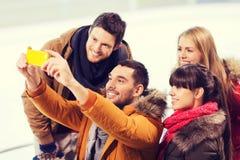 Amis heureux avec le smartphone sur la piste de patinage Photos libres de droits