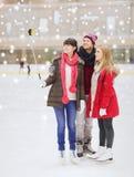 Amis heureux avec le smartphone sur la piste de patinage Photographie stock libre de droits