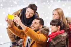 Amis heureux avec le smartphone sur la piste de patinage Images stock