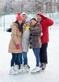 Amis heureux avec le smartphone sur la piste de patinage de glace Image stock
