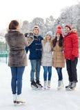 Amis heureux avec le smartphone sur la piste de patinage de glace Image libre de droits