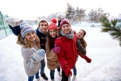 Amis heureux avec le smartphone sur la piste de patinage de glace Photos stock