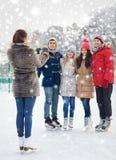 Amis heureux avec le smartphone sur la piste de patinage de glace Photo stock