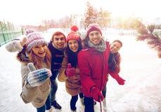 Amis heureux avec le smartphone sur la piste de patinage de glace Photographie stock