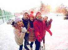 Amis heureux avec le smartphone sur la piste de patinage de glace Images libres de droits