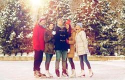 Amis heureux avec le smartphone sur la piste de patinage de glace Photographie stock libre de droits