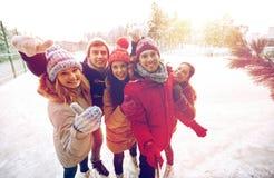 Amis heureux avec le smartphone sur la piste de patinage de glace Images stock
