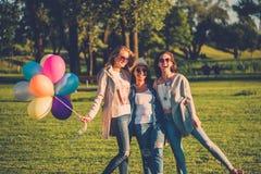 Amis heureux avec les ballons à air de couleur arc-en-ciel en parc Image stock