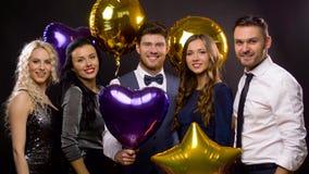 Amis heureux avec les ballons d'or et violets banque de vidéos