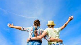 Amis heureux avec les bras ouverts sous le ciel bleu Photos libres de droits