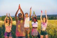 Amis heureux avec les bras tendus et poudre colorée sur l'habillement au festival de holi Photographie stock libre de droits