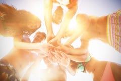 Amis heureux avec les mains empilées contre le ciel Image stock