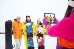 Amis heureux avec les surfs des neiges et le PC de comprimé Image libre de droits