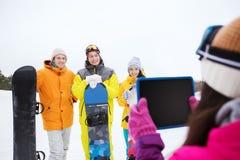 Amis heureux avec les surfs des neiges et le PC de comprimé Photographie stock libre de droits
