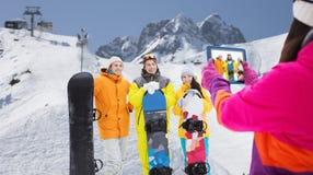 Amis heureux avec les surfs des neiges et le PC de comprimé Photos libres de droits