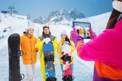 Amis heureux avec les surfs des neiges et le PC de comprimé Photographie stock