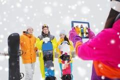Amis heureux avec les surfs des neiges et le PC de comprimé Photo libre de droits