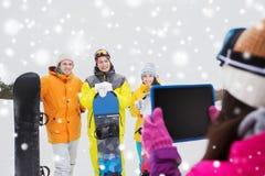 Amis heureux avec les surfs des neiges et le PC de comprimé Photos stock