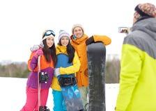 Amis heureux avec les surfs des neiges et le smartphone Images stock