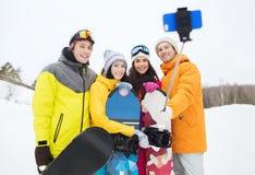 Amis heureux avec les surfs des neiges et le smartphone Image libre de droits