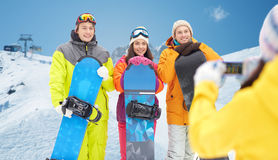 Amis heureux avec les surfs des neiges et le smartphone Photo stock