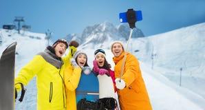 Amis heureux avec les surfs des neiges et le smartphone Image stock