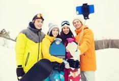 Amis heureux avec les surfs des neiges et le smartphone Photos libres de droits